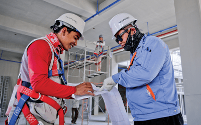 two construction workers looking over contract