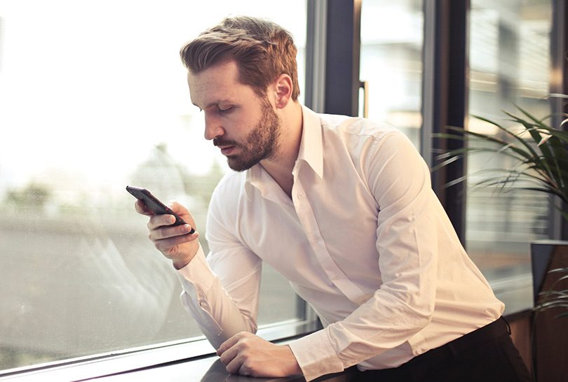 Man reading news article on cell phone